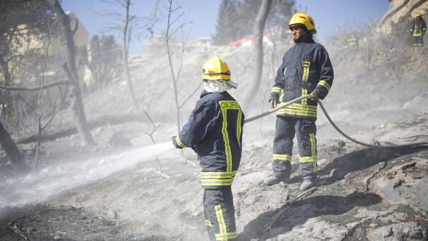 Firefighters damp down a blaze that forced tens of thousands of people to flee their homes (AP)