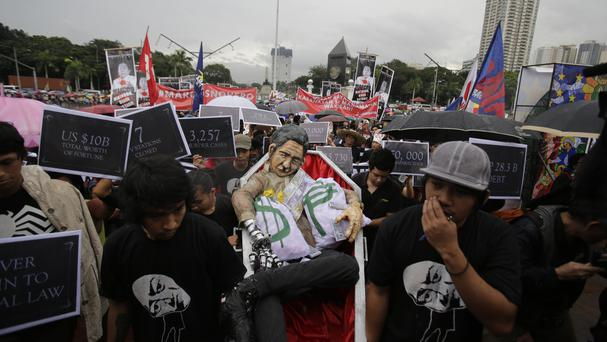 Protesters carry an effigy of dictator Ferdinand Marcos during a rally at Manila's Rizal Park (AP)