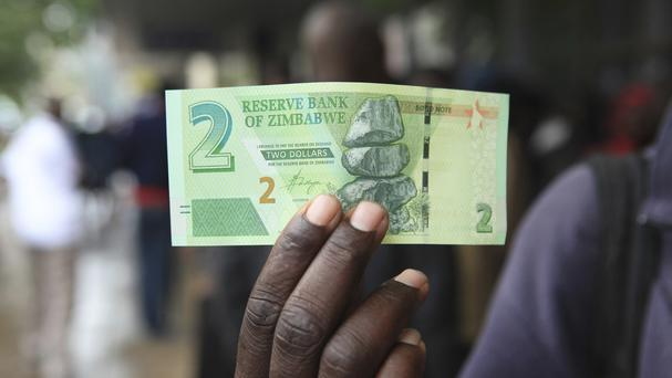 A man shows a new note introduced by the Reserve Bank of Zimbabwe in Harare (AP)