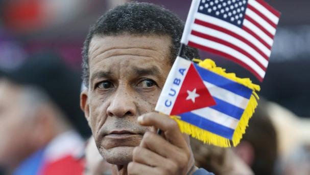 Ramon Gonzalez waves Cuban and American flags at the rally (AP)