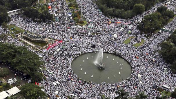 Protesters fill the streets around the National Monument during a rally against Jakarta's governor (AP)