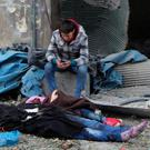 A Syrian boy sits next to bodies after artillery fire struck the Jub al-Quba district in Aleppo, Syria, last month. Syrian activists said at least 21 people were killed in the artillery barrage on the housing area. Photo: AP