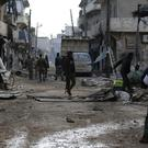 Syrian army soldiers patrol the east Aleppo neighbourhood of Tariq al-Bab (AP)
