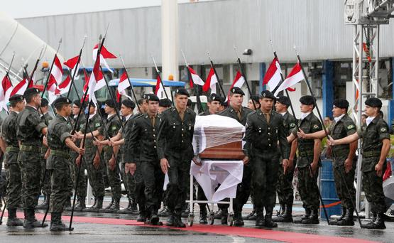 DISASTER: Military personnel carry a coffin containing the remains of a victim of the plane crash in Colombia during arrival in Chapeco, Brazil. Photo: Paulo Whitaker/Reuters