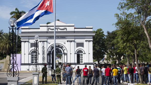 People stand at the entrance of the Santa Ifigenia cemetery where the ashes of Fidel Castro were interred in Santiago, Cuba (AP)
