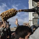 An Iraqi man distributes potatoes to civilians in the Samah district of Mosul (AP)