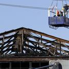 A search and rescue team is lowered into the site of the warehouse fire (AP)