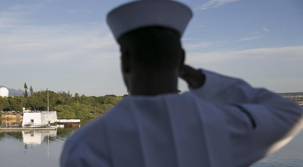 A Navy sailor salutes the USS Arizona memorial (AP)