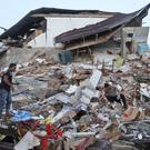 Rescuers survey the damage after an earthquake in Ulhee Glee, Aceh province (AP)