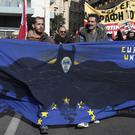 Protesters hold a banner during a rally in Athens (AP)