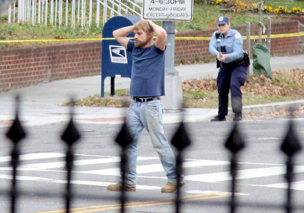 Hands up: Edgar Welch (28) surrenders to police in Washington. Welch, who said he was investigating a conspiracy theory about Hillary Clinton running a child sex ring out of a pizza place, fired an assault rifle inside the restaurant on Sunday, injuring no one