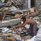 A resident clears rubble from the ruin of his house in Pidie Jaya (AP)