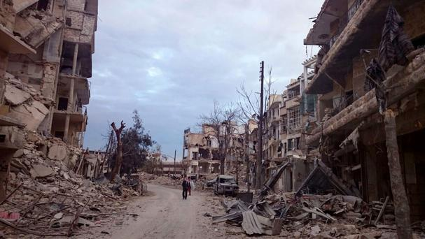 Men walk past damaged buildings and shops in the eastern Aleppo neighbourhood of al-Mashhad (Wissam Zarqa, via AP)