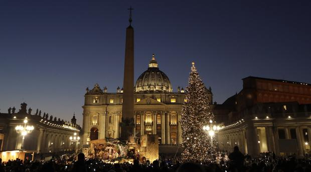 The Christmas tree and nativity scene are lit up in St Peter's Square (AP)
