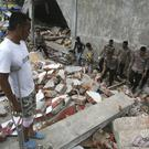 Survivors and police officers clear the rubble in Tringgading, Aceh province (AP)