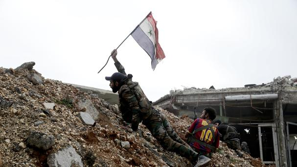 A Syrian army soldier places a flag during a battle with rebel fighters at the Ramouseh front line, east of Aleppo (AP)