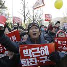Protesters holding signs reading 'arrest Park Geun-hye' shout as they march toward the presidential house in Seoul (AP)