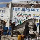 A Somali man sits next to the remains of his partially destroyed fuel shop near the scene of a suicide car bomb attack in Mogadishu (AP)