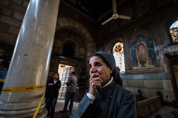 A nun reacts as security forces inspect the scene after a bomb ripped through Cairo's Al-Bortosia chapel, killing at least 25 worshippers during Sunday Mass and injuring scores more Photo: AFP