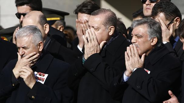 Turkey's President Recep Tayyip Erdogan, centre, Prime Minister Binali Yildirim, left, and former president Abdullah Gul, right, at a memorial for police officers killed outside the Besiktas football stadium in Istanbul (AP)