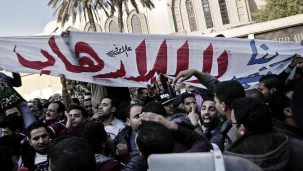 Coptic Christians hold a banner which reads 'No to terrorism' in Arabic during a protest outside St Mark's Cathedral in Cairo following a deadly bomb attack (AP)