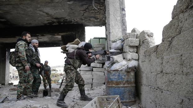 Syrian army soldiers fire their weapons during a battle with insurgents at the Ramouseh front line, east of Aleppo, Syria.