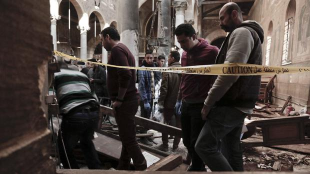 Security forces examine the scene inside the St Mark Cathedral in central Cairo (AP)
