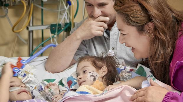 Eva, left, and Erika Sandoval meet for the first time since their separation surgery with their parents Arturo and Aida (Lucile Packard Children's Hospital Stanford/AP)