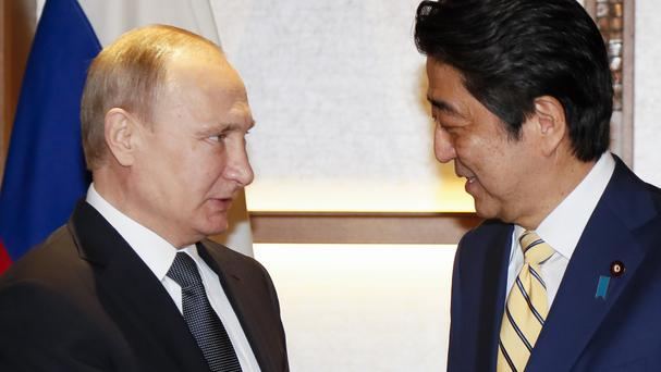 Japanese prime minister Shinzo Abe and Russian president Vladimir Putin speak to each other during their meeting at a hot springs resort in Nagato, western Japan (AP)