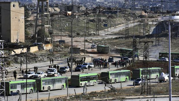 People gather near green government buses to be evacuated from eastern Aleppo (SANA/AP)