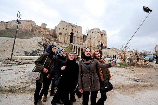 Women take a selfie outside Aleppo's historic citadel, in the government controlled area of the city, Syria December 17, 2016. Photo: REUTERS/ Omar Sanadiki