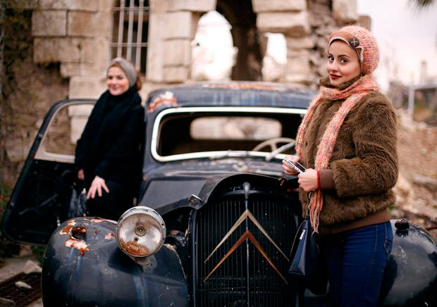 Women pose for a picture at the entrance of the Carlton Hotel, in the government controlled area of Aleppo, Syria December 17, 2016. Photo: REUTERS/ Omar Sanadiki