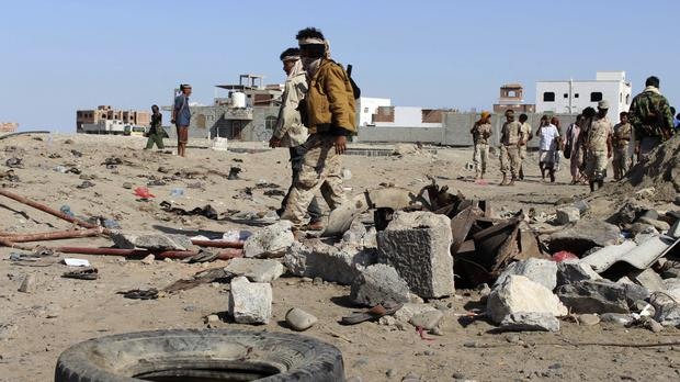 Soldiers gather at the site of a suicide bomb at a base in the southern city of Aden, Yemen (AP)