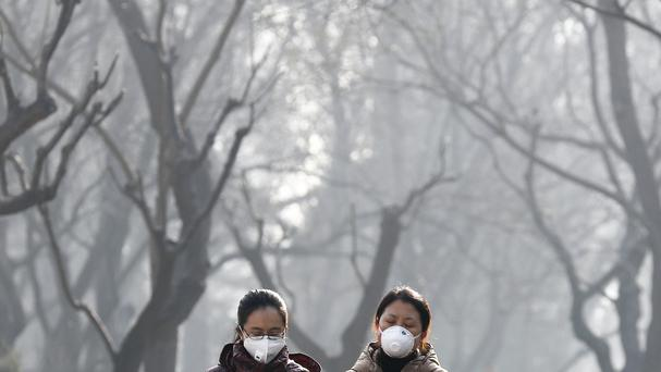 Chinese women wearing masks for protection against air pollution walk through Ritan Park shrouded by dense smog in Beijing. (AP Photo/Andy Wong)