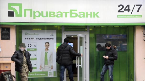 A client enters PrivatBank as other clients stand by in the centre Kiev, Uraine (AP)