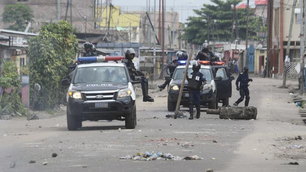 Riot police remove barricades used to block a road during a protest in Kinshasa (AP/John Bompengo)