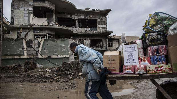 A street vendor pulls his cart in front of a house damaged by fighting in Mishraq district in Mosul, Iraq (AP)