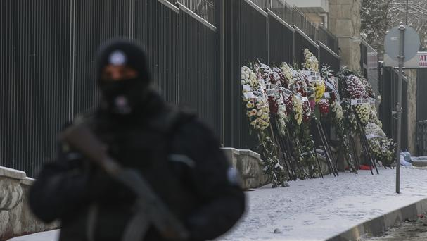 Wreaths are left on the the road leading to the Russian embassy in Ankara, Turkey, as a Turkish police officer secures the road (AP)