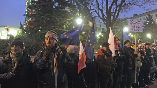 Protesters stand along a fence in front of the parliament in Warsaw (AP)