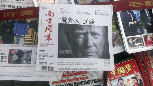 A front page of a Chinese newspaper with a photo of Donald Trump and the headline