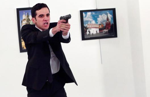 assassin: Mevlut Mert Altintas pictured moments after shooting Andrei Karlov, Russia's Ambassador to Turkey