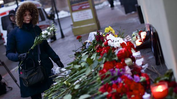 A woman leaves flowers in Moscow (AP)