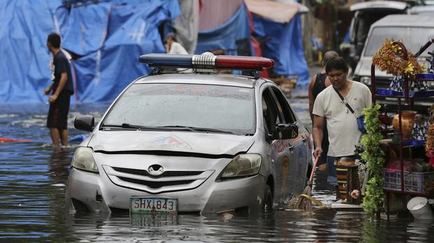 A police car is parked in a flooded street caused by rains from Typhoon Nock-Ten in Quezon city (AP/Aaron Favila)