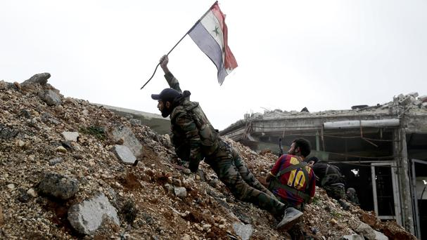 A Syrian army soldier places a Syrian national flag during a battle with rebel fighters east of Aleppo (AP)