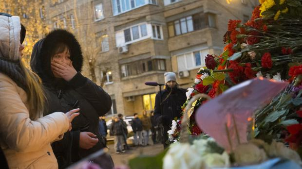 Tears as women place flowers in front of the Alexandrov Ensemble building in Moscow (AP)