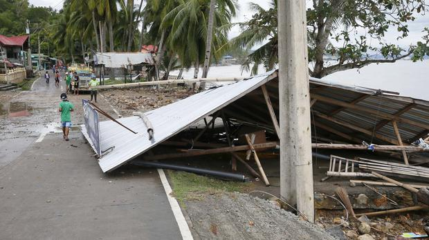 The roof of a store partially blocks the road after Typhoon Nock-Ten in Mabini township (AP)