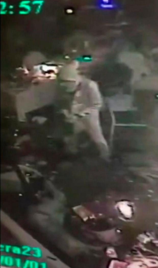 An attacker carrying a gun walks in the nightclub in Istanbul, early Sunday, Jan. 1, 2017. An assailant believed to have been dressed in a Santa Claus costume opened fire at a crowded nightclub in Istanbul during New Year's celebrations, killing dozens of people and wounding tens of others in what the province's governor described as a terror attack. (Haberturk Gazetesi Yildirim Ekspresi via AP) )