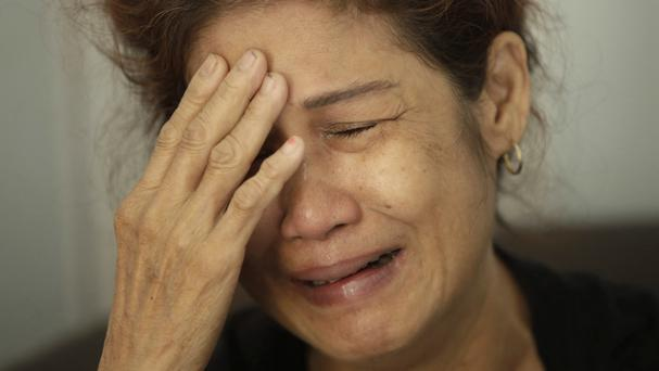 A family member weeps as she waits for the identification process of the victims (AP)