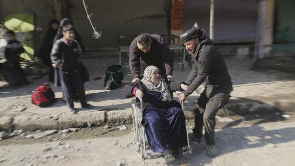 Soldiers help an elderly woman as she and her family flee fighting between Iraqi security forces and Islamic State militants in Mosul (AP)