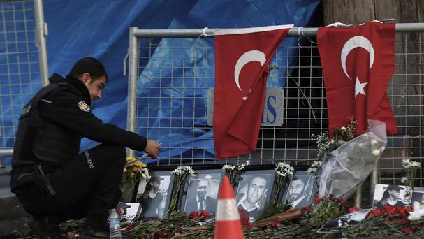 A police officer looks at photographs of the victims after the attack at a nightclub in Istanbul (AP)